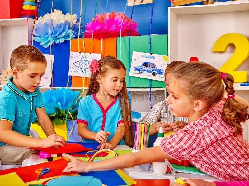 Scherzen Sie das Halten des farbigen Papiers auf Tabelle im Kindergarten lizenzfreies stockbild