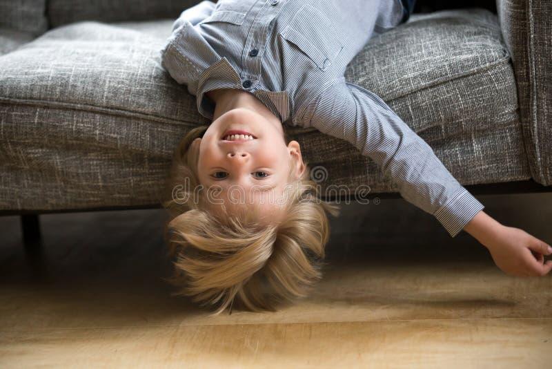 Scherzen Sie das Jungenlügen, das auf dem Sofa umgedreht ist, das Kamera betrachtet lizenzfreies stockbild