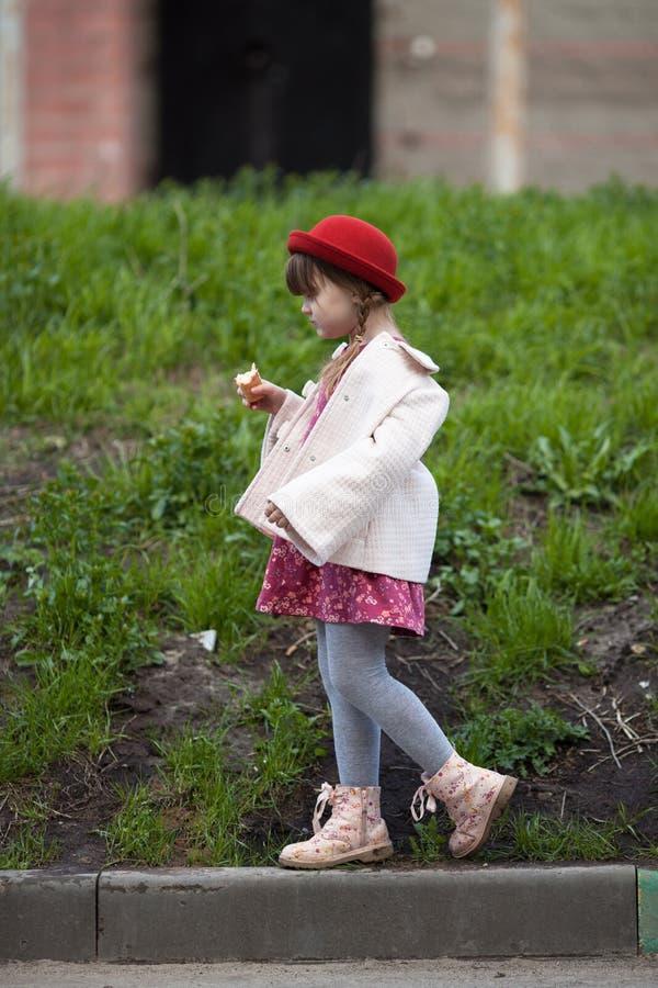 Scherzen Sie das Mädchen mit Zöpfen im Hut Eiscreme und Wege essend stockfoto