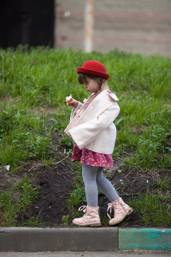 Scherzen Sie das Mädchen mit Zöpfen im Hut Eiscreme und Wege essend lizenzfreies stockbild