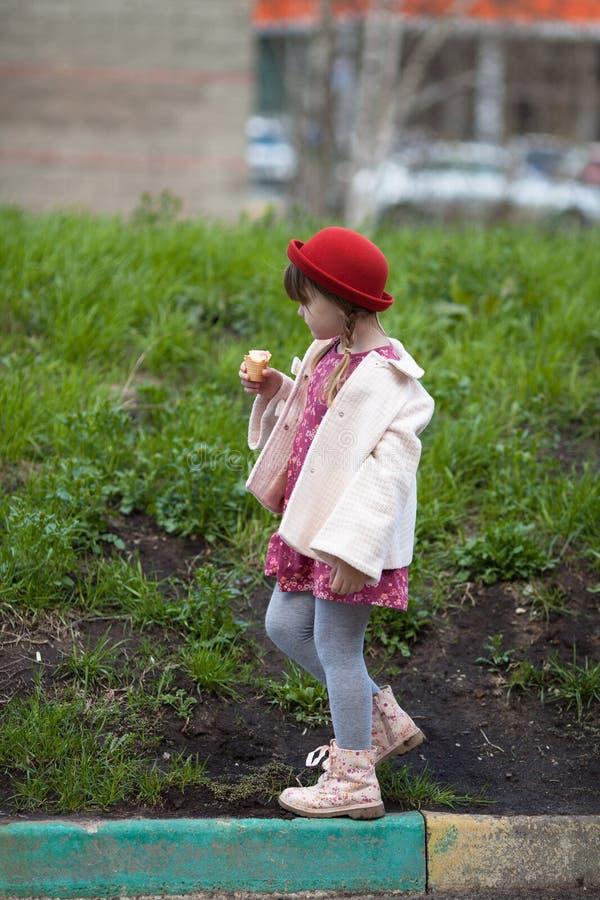 Scherzen Sie das Mädchen mit Zöpfen im Hut Eiscreme und Wege essend stockbild