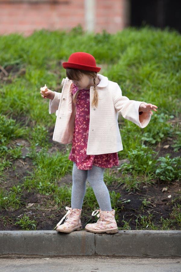 Scherzen Sie das Mädchen mit Zöpfen im Hut Eiscreme und Wege essend lizenzfreie stockfotos