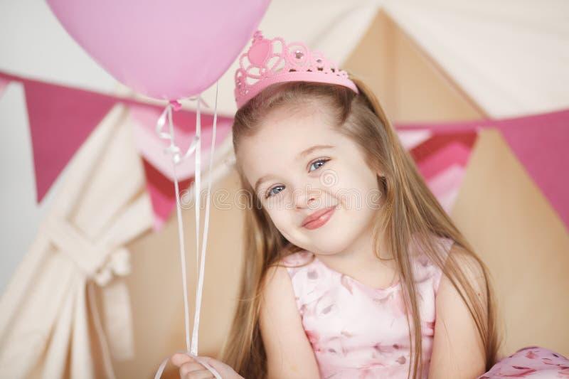 Scherzen Sie das Mädchen, welches die rosa Krone trägt, die ihren Geburtstag feiert lizenzfreies stockfoto
