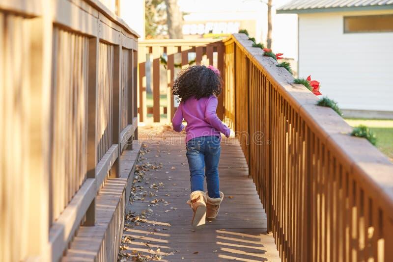 Scherzen Sie das Mädchenkleinkind, welches das Laufen in hintere Ansicht des Parks spielt lizenzfreie stockfotografie
