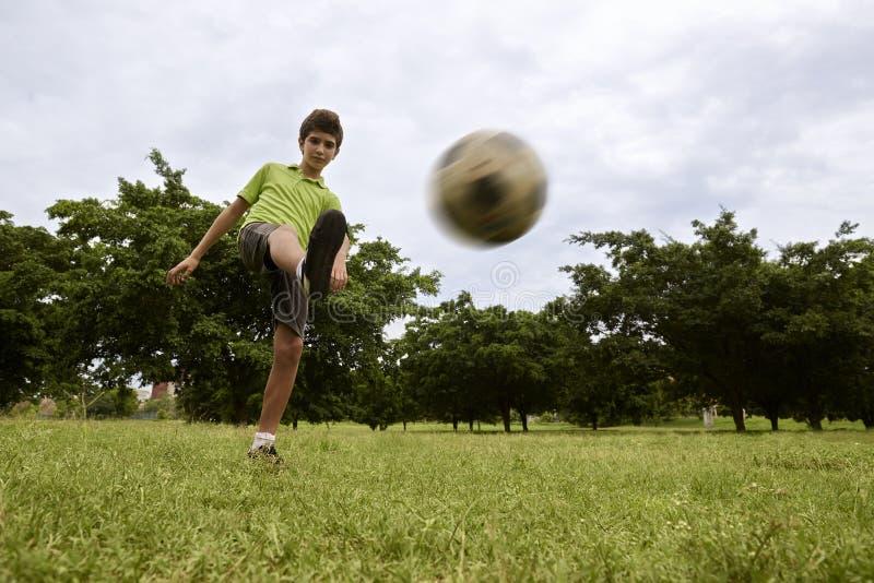 Scherzen Sie das Spielen des Fußball- und Fußballspiels im Park lizenzfreie stockbilder