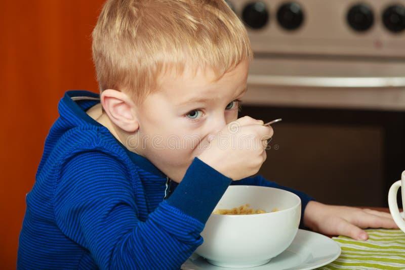 Scherzen Sie den Jungen, der Frühstück, Getreide und Milch in der Schüssel isst lizenzfreies stockbild