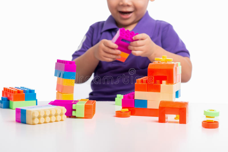 Scherzen Sie den Jungen, der mit Blöcken vom lokalisierten Spielzeugerbauer spielt lizenzfreie stockfotos