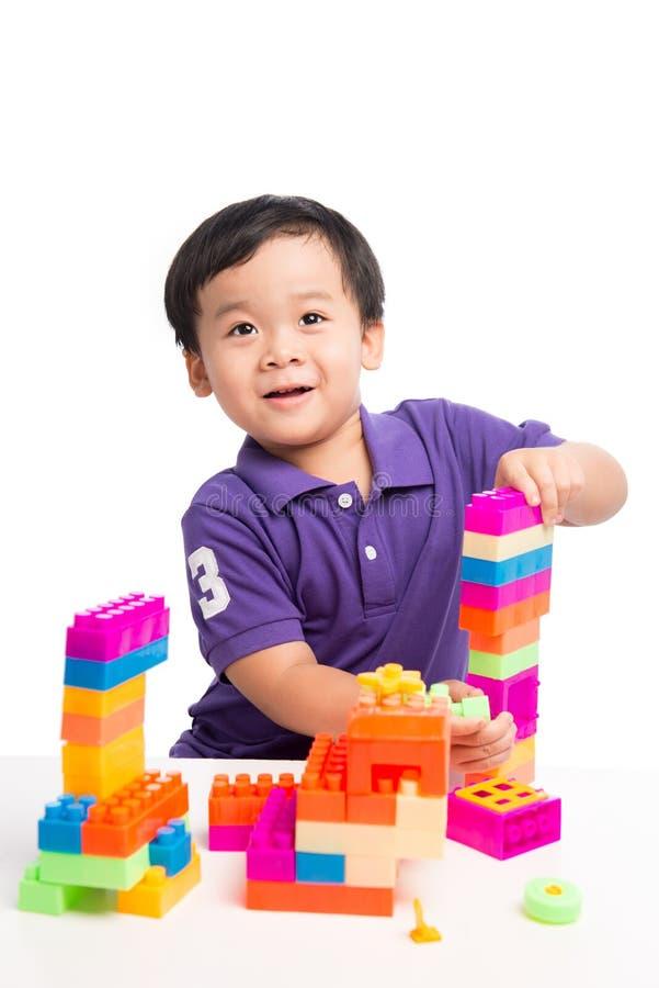 Scherzen Sie den Jungen, der mit Blöcken vom lokalisierten Spielzeugerbauer spielt stockfotografie