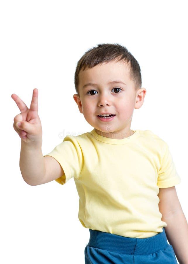 Scherzen Sie den Jungen, der Sieghandzeichen auf weißem backgro zeigt stockfotografie