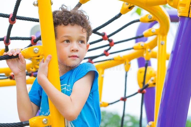 Scherzen Sie den Jungen, der Spaß, um auf Kind-` s kletterndem Spielplatz Spielzeugs, zurück zu Schulaktivität in der Schule zu s lizenzfreies stockbild