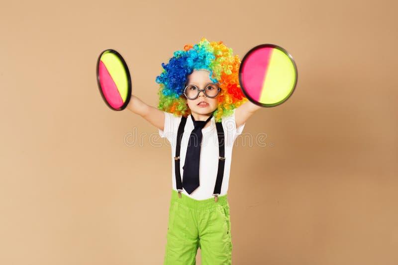 Scherzen Sie in der Clownperücke und -brillen, die Fangballspiel spielen lizenzfreie stockfotografie