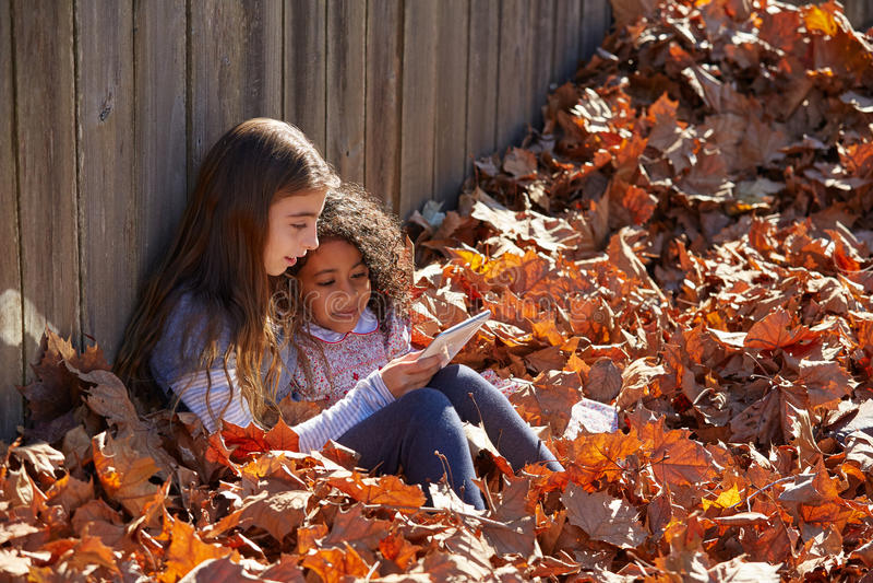 Scherzen Sie die Freundinnen, die Tabletten-PC im Herbstlaub spielen stockfotos