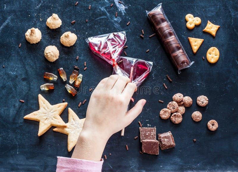 Scherzen Sie die Hand, die für Bonbons - glücklichen Kindheitstraum erreicht stockbilder