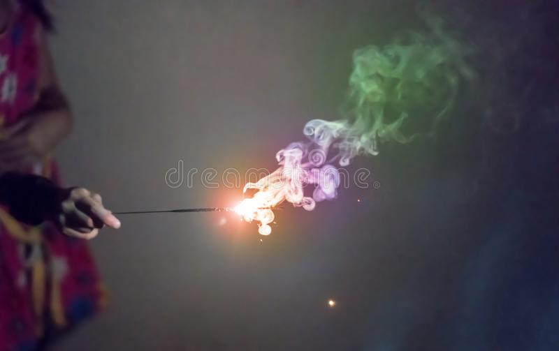 Scherzen Sie die Hand, die ein brennendes Wunderkerzefeuerwerkslicht hält stockfotos