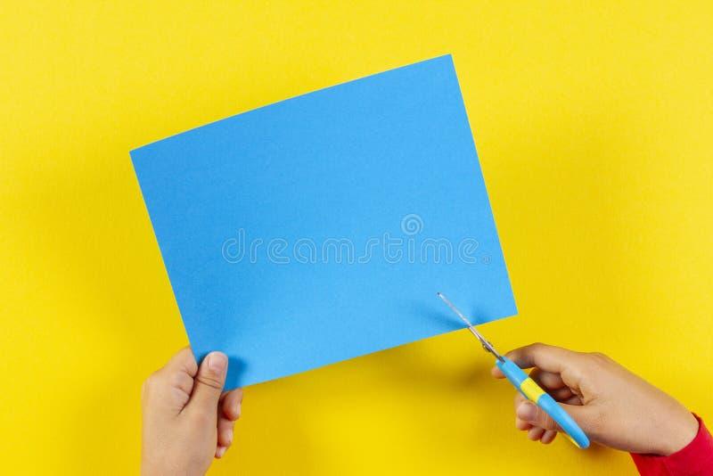 Scherzen Sie ` s Hände, die farbiges Papier mit Scheren schneiden lizenzfreie stockfotos