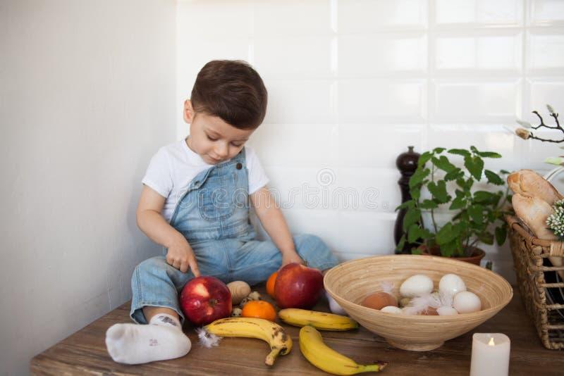 Scherzi avere una tavola in pieno di alimento biologico Bambino allegro che mangia insalata sana e frutti Bambino che sceglie fra immagini stock