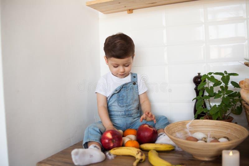 Scherzi avere una tavola in pieno di alimento biologico Bambino allegro che mangia insalata sana e frutti Bambino che sceglie fra fotografia stock