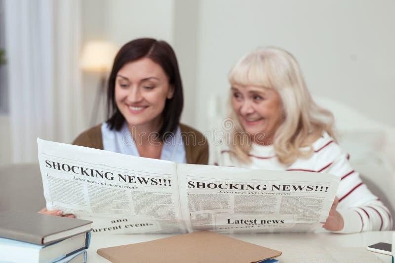 Scherzi esuberanti della lettura del badante e della donna più anziana fotografia stock libera da diritti
