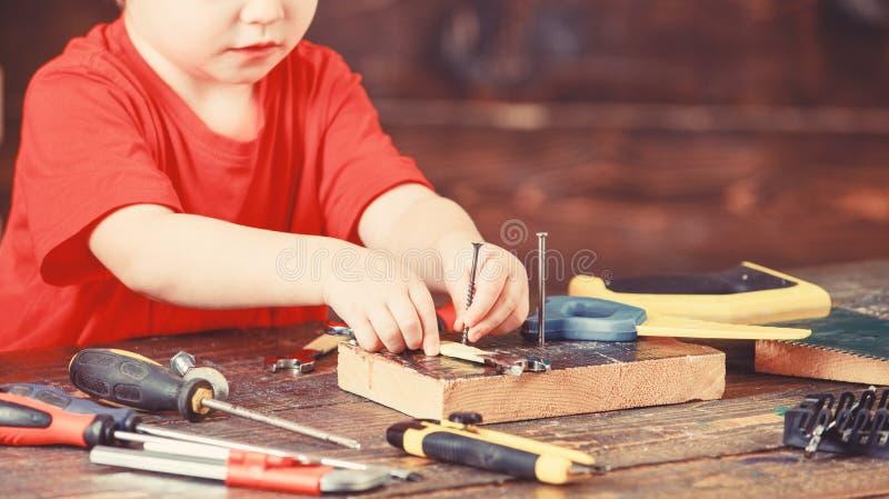 Scherzi gli impianti anonimi con il cacciavite, il fondo di legno, fine su Concetto educativo del gioco Gioco da bambini come cos fotografia stock