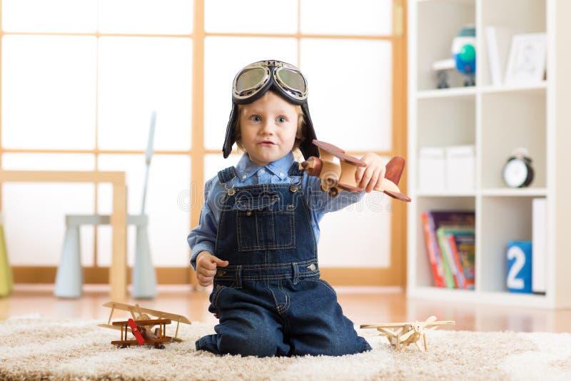 Scherzi i giochi del casco dell'aviatore weared ragazzo con l'aereo di legno del giocattolo nella sua stanza di bambini immagine stock