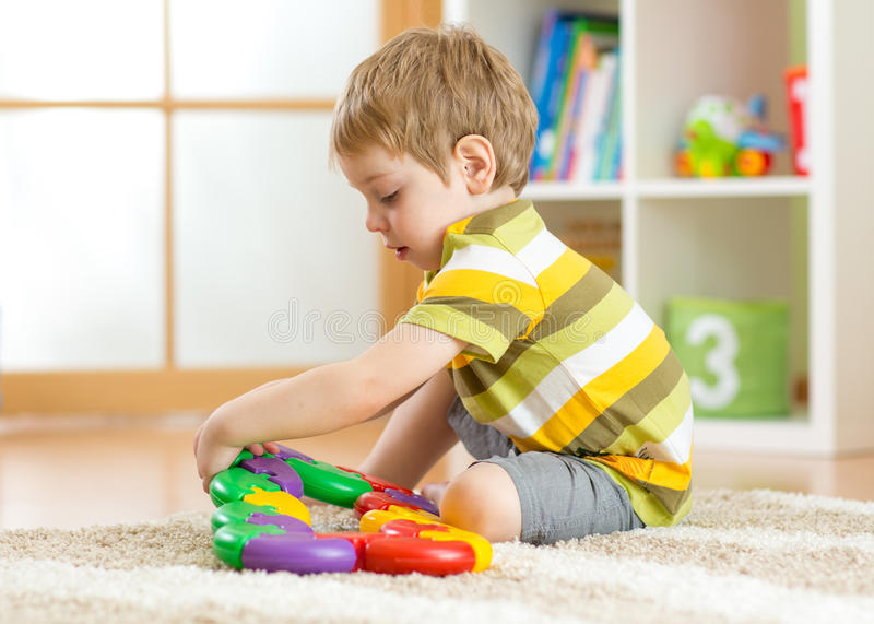 Scherzi i giochi del ragazzino con un multi puzzle colorato in scuola materna fotografia stock libera da diritti