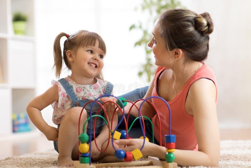 Scherzi i giochi della ragazza con il giocattolo educativo in scuola materna a casa Madre felice che esamina sua figlia astuta fotografia stock libera da diritti