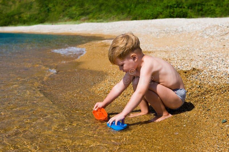 Scherzi il gioco con i giocattoli variopinti sulla spiaggia del mare immagine stock