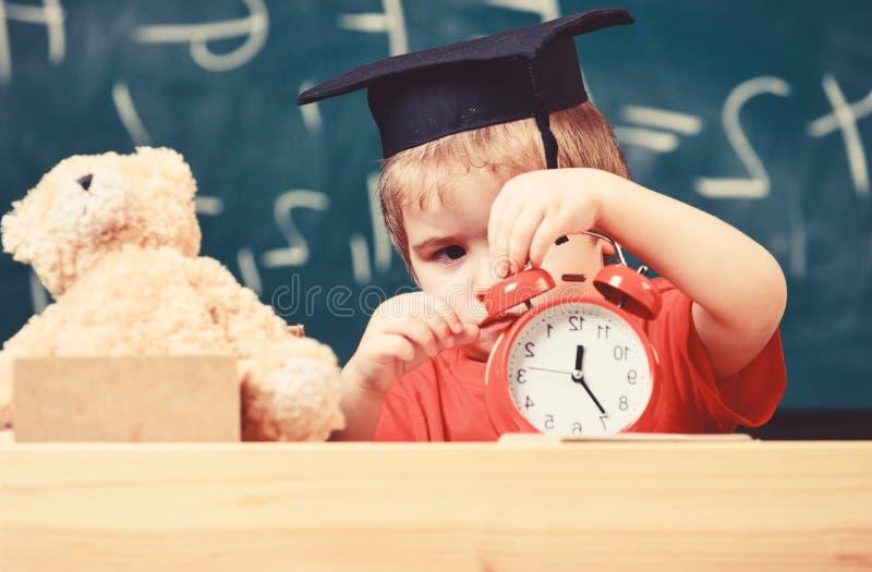 Scherzi il ragazzo in cappuccio accademico vicino al microscopio, tenute cronometrano in aula, lavagna su fondo Il bambino sul fr immagini stock libere da diritti