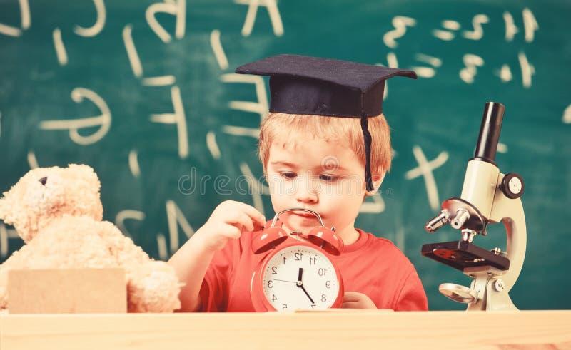 Scherzi il ragazzo in cappuccio accademico vicino al microscopio, tenute cronometrano in aula, lavagna su fondo Scuola aspettante fotografia stock