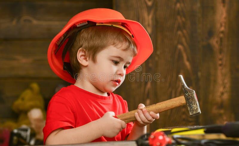 Scherzi il ragazzo che martella il chiodo nel bordo di legno Bambino nel gioco sveglio del casco come il costruttore o riparatore immagine stock