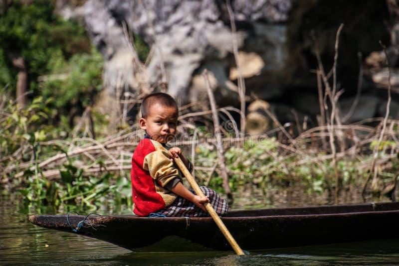 Scherzi l'aiuto del suo papà che rema la sua piroga tradizionale fuori della caverna sadan, Hpa-an, il distretto di Hpa-an, Myanm fotografia stock libera da diritti