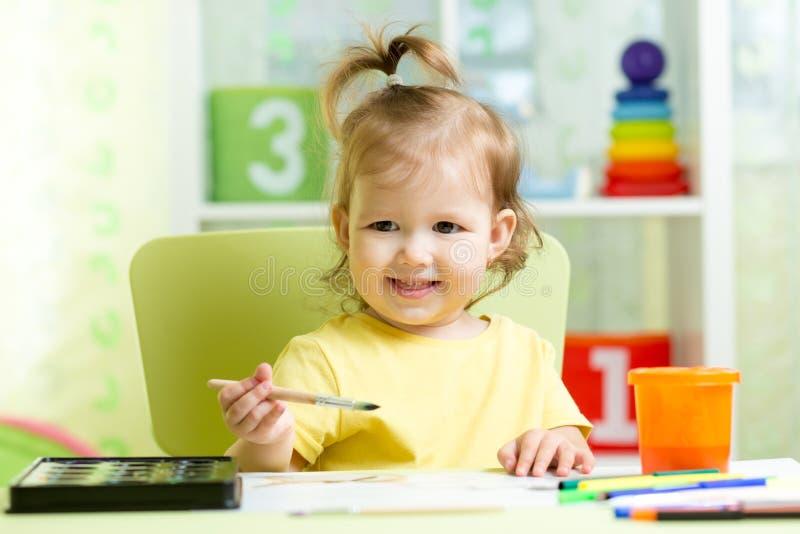 Scherzi la pittura della ragazza con gli acquerelli a casa o la scuola materna prescolare immagini stock libere da diritti