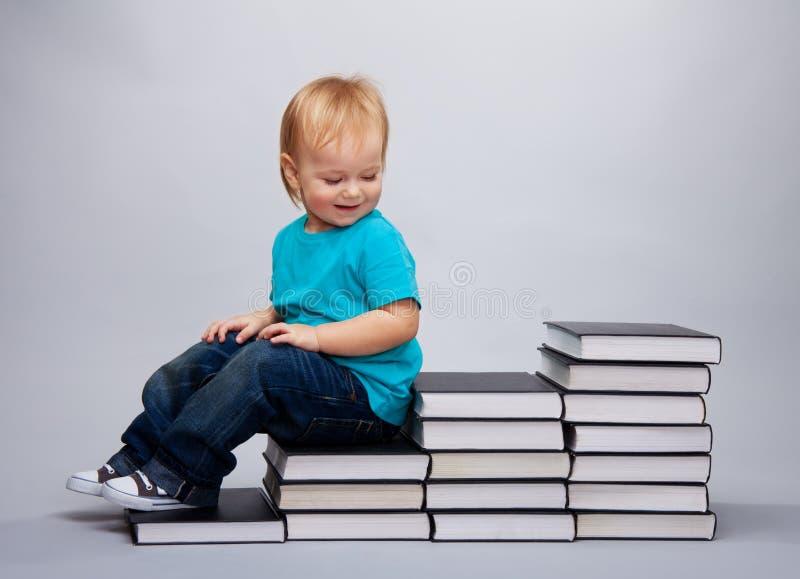 Scherzi la seduta su un dei punti fatti dei libri immagine stock