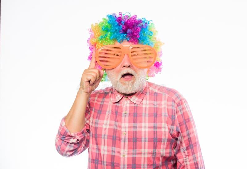 Scherzo piacevole Pagliaccio anziano Persona allegra barbuta senior dell'uomo indossare parrucca variopinta e gli occhiali da sol fotografia stock