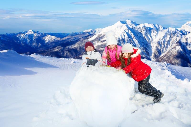 Scherzt Balling herauf den enormen Schneeball, der einen Schneemann macht lizenzfreie stockfotos