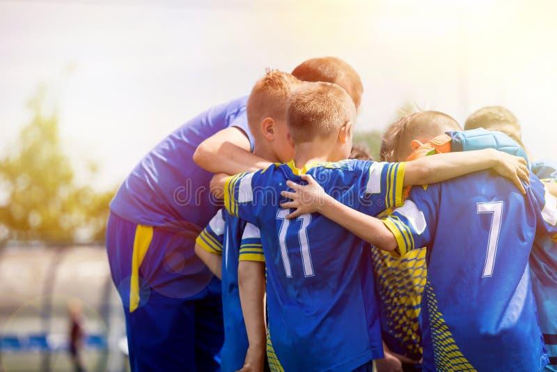 Scherzt das Sportteam, das aufmunternde Wörter mit Trainer hat Kinderfußballteam motiviert vom Trainer Anleitung des Fußballjugen lizenzfreie stockfotos