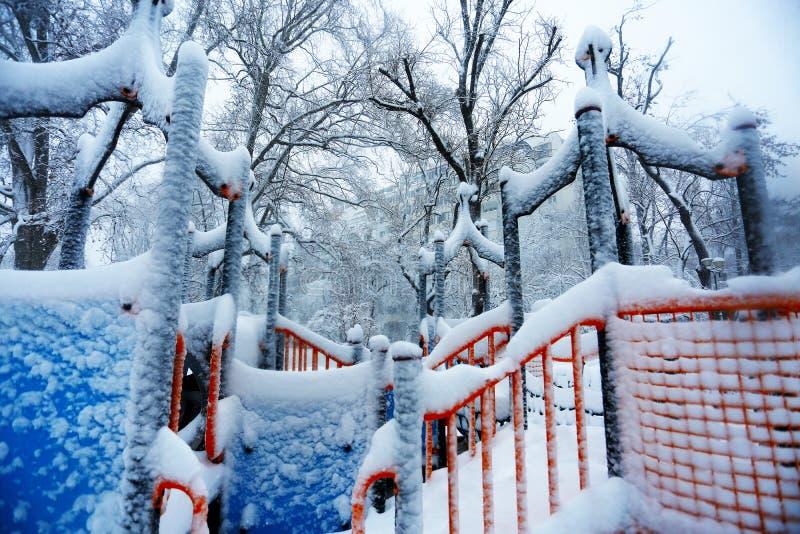 Scherzt den Spielplatz, der mit Schnee bedeckt wird stockfoto