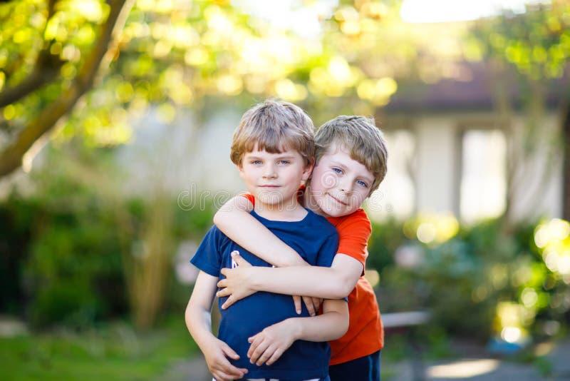 Scherzt kleine aktive Schule zwei die Jungen, Zwillinge und Geschwister, die am Sommertag umarmen lizenzfreie stockbilder