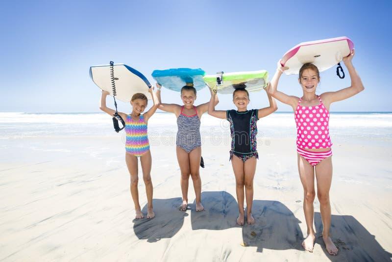 Scherzt zusammen spielen am Strand während im Urlaub stockbild