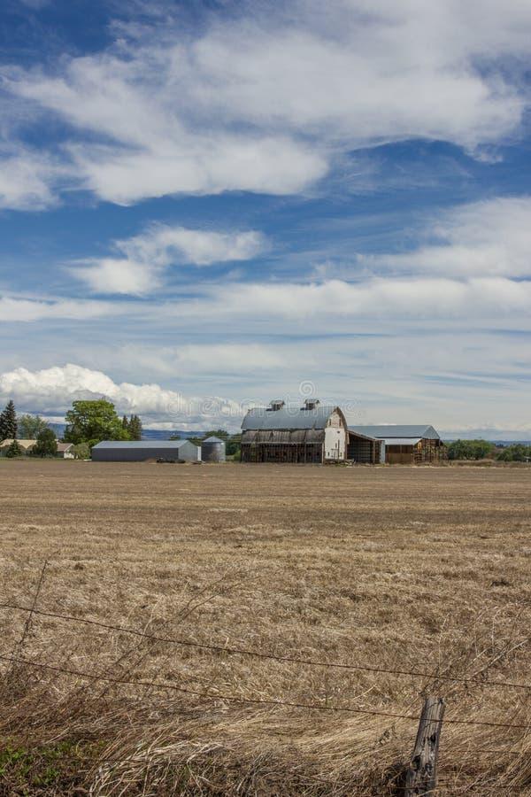 Scheune und Felder unter einem blauen Himmel voll von Wolken lizenzfreies stockfoto