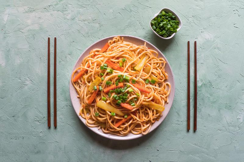 Schezwan Noodles with vegetables in a plate on a green table. Top view. Hakka Noodles is a popular Indo-Chinese recipes.  stock image