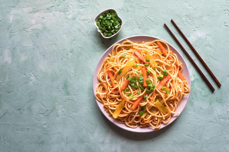 Schezwan Noodles with vegetables in a plate on a green table. Top view. Hakka Noodles is a popular Indo-Chinese recipes.  royalty free stock photos