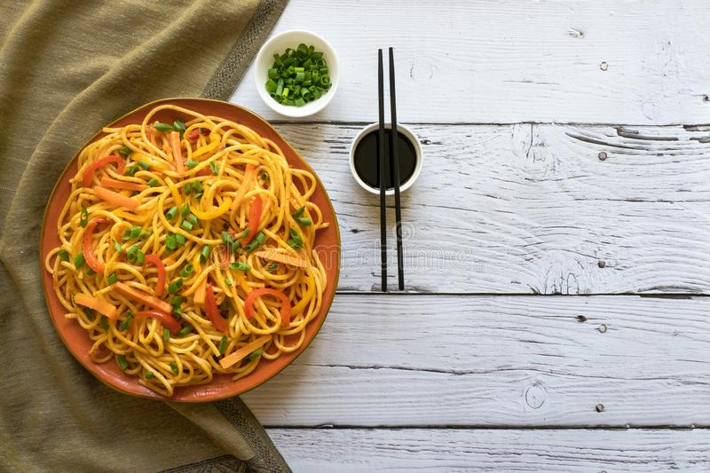 Schezwan Noodles with vegetables in a plate on a wooden table. Top view. Hakka Noodles is a popular Indo-Chinese recipes. Schezwan Noodles with vegetables in a royalty free stock photography