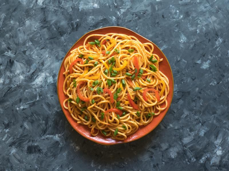 Schezwan Noodles with vegetables in a plate on a wooden table. Top view. Hakka Noodles is a popular Indo-Chinese recipes. Schezwan Noodles with vegetables in a stock photos