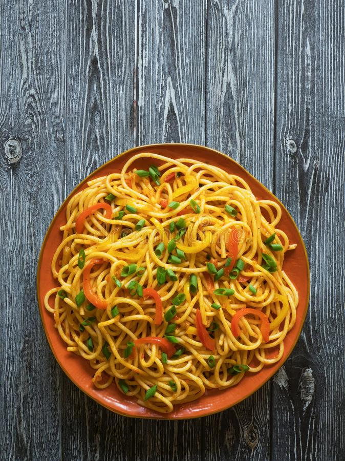 Schezwan Noodles with vegetables in a plate on a wooden table. Top view. Hakka Noodles is a popular Indo-Chinese recipes. Schezwan Noodles with vegetables in a royalty free stock photos