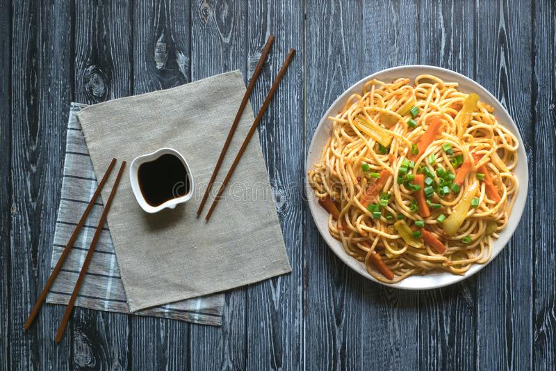 Schezwan Noodles with vegetables in a plate on a wooden table. Top view. Hakka Noodles is a popular Indo-Chinese recipes.  stock images