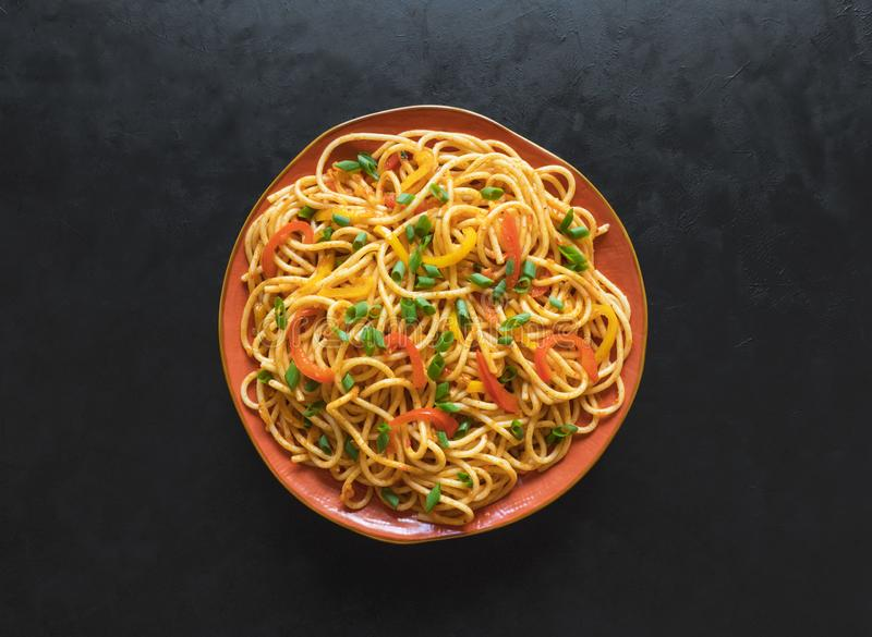 Schezwan Noodles with vegetables in a plate on a wooden table. Top view. Hakka Noodles is a popular Indo-Chinese recipes. Schezwan Noodles with vegetables in a stock photo