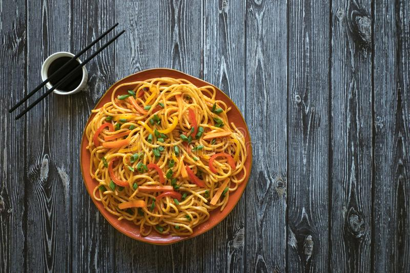 Schezwan Noodles with vegetables in a plate on a wooden table. Top view. Hakka Noodles is a popular Indo-Chinese recipes. Schezwan Noodles with vegetables in a royalty free stock photo