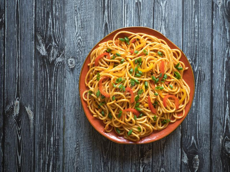 Schezwan Noodles with vegetables in a plate on a wooden table. Top view. Hakka Noodles is a popular Indo-Chinese recipes. Schezwan Noodles with vegetables in a stock image