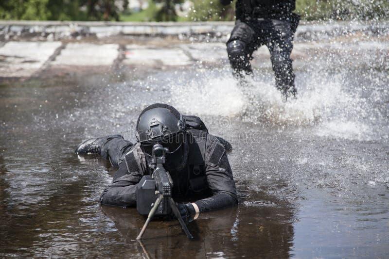 SCHIAFFO degli ufficiali di polizia dei ops di spec. nell'acqua fotografie stock libere da diritti
